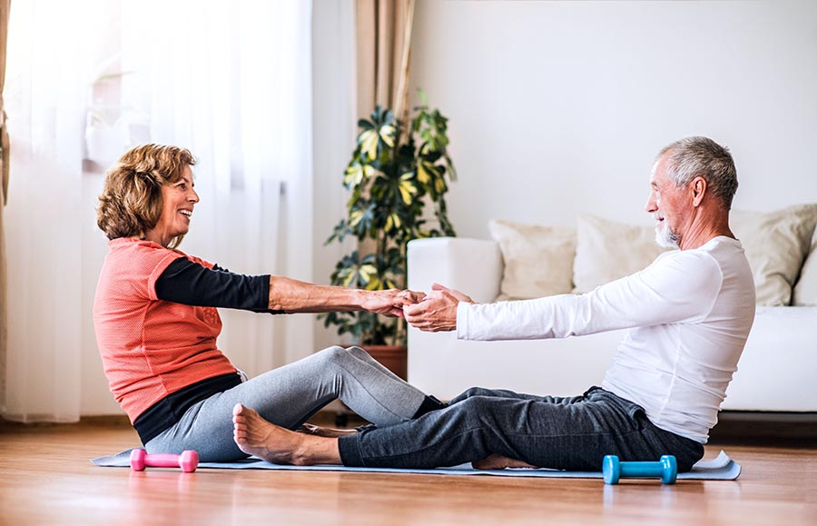 Happy senior couple doing exercise at home.